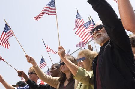 gente saludando: Aglomero sosteniendo banderas norteamericanas