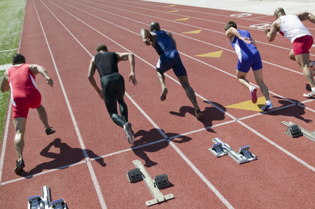 Male sprinters leaving starting blocks Stock Photo - 5475772