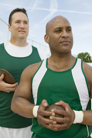 Two male athletes holding shot and discus Stock Photo - 5475808