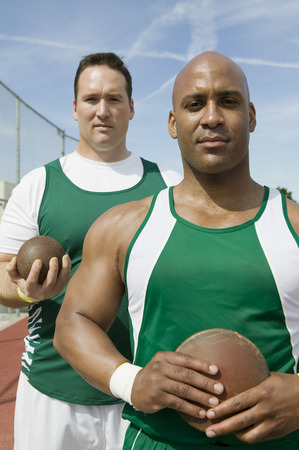 Two male athletes holding shot and discus, portrait Stock Photo - 5475809