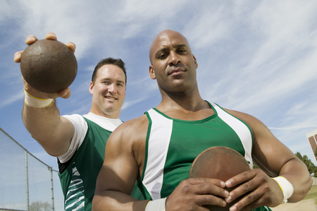 Two male athletes holding shot and discus, portrait Stock Photo - 5475810