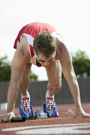 relay baton: Young man in starting blocks holding relay baton