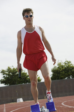 Young man by starting blocks holding relay baton Stock Photo - 5475822