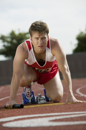 Young man in starting blocks holding relay baton, portrait Stock Photo - 5475823