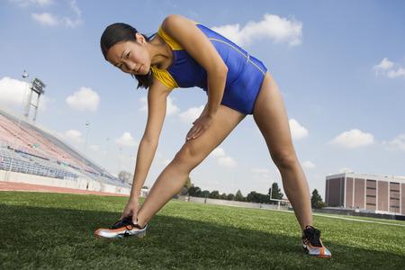 legs apart: Atleta femenina que se extiende, retrato  LANG_EVOIMAGES