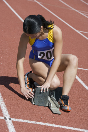 Female athlete stetting up starting block Stock Photo - 5475876