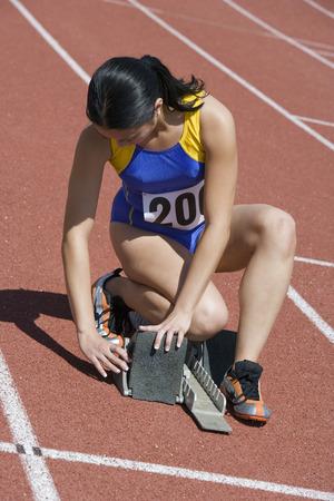 Female athlete stetting up starting block Stock Photo - 5475876