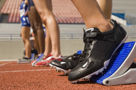 Group of female track athletes on starting blocks, close-up view Stock Photo - 5476002