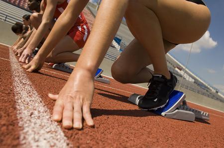 Group of female track athletes on starting blocks Stock Photo - 5476003