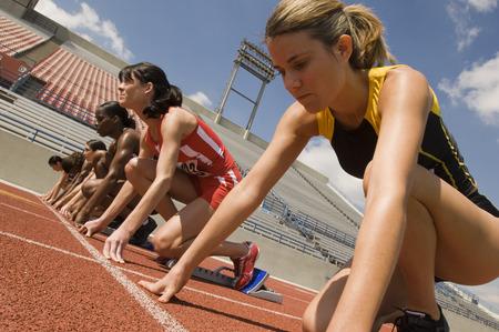 Group of female track athletes on starting blocks Stock Photo - 5476004