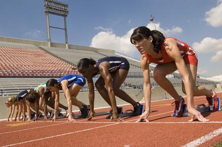 Group of female track athletes on starting blocks Stock Photo - 5476005