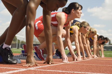スターティング ブロックの女性の陸上競技選手のグループ 写真素材