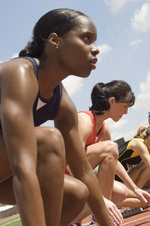 Group of female track athletes on starting blocks Stock Photo - 5476012