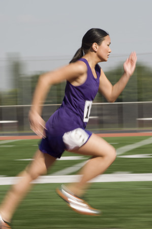 Female track athlete sprinting Stock Photo - 5476019