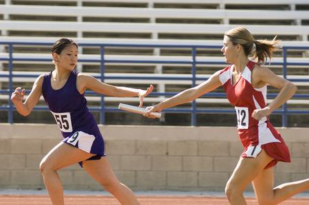 relevos: Mujer atleta pasa batuta relevo a otro