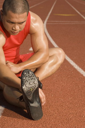 Male athlete stretching on track Stock Photo - 5476051