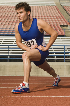 Runner on a track, stretching Stock Photo - 5476063