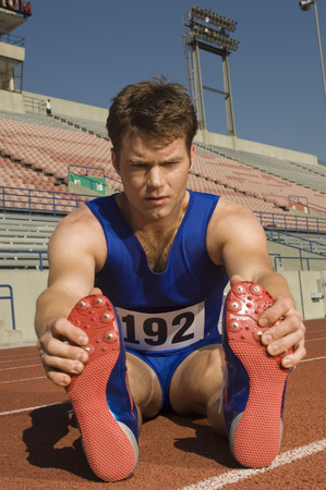 Runner on a track, stretching Stock Photo - 5476066
