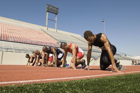 kneel down: Runners waiting in starting blocks on track LANG_EVOIMAGES