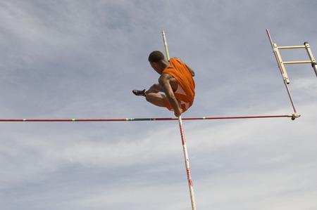 Pole vaulted in mid-air, low angle view Stock Photo - 5476089