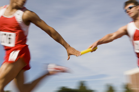 Athletes passing relay baton