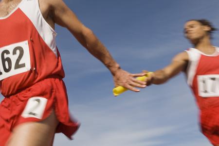 Athletes passing relay baton Stock Photo - 5476095
