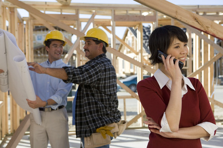 Woman using mobile phone near workers on construction site Stock Photo - 5476128