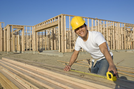 wooden beams: Construction worker measuring wooden planks