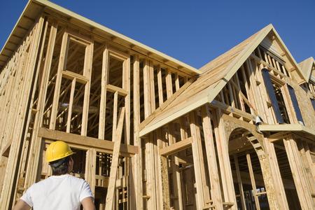 construction frame: Construction worker observing unfinished house