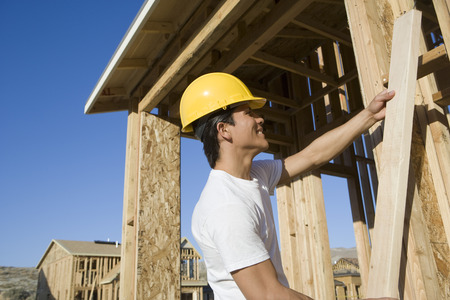 wooden beams: Construction worker holding wooden beam LANG_EVOIMAGES