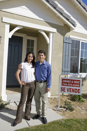 Young couple in front of new house Stock Photo - 5476145