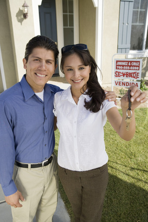 Young couple holding keys outside new home, portrait Stock Photo - 5476149