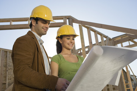 Young couple examining blueprint in construction site LANG_EVOIMAGES