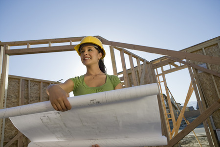 Young woman examining blueprint in construction site Stock Photo - 5476186