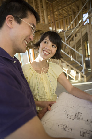 Couple over blueprint in construction site Stock Photo - 5476251