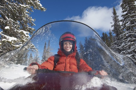 late thirties: Smiling Woman Behind Windshield of Snowmobile LANG_EVOIMAGES