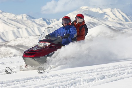holidaying: Couple Snowmobiling with Mountains in Background LANG_EVOIMAGES