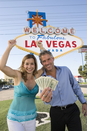 Mid-adult couple in front of Welcome to Las Vegas sign, portrait Stock Photo - 5476286