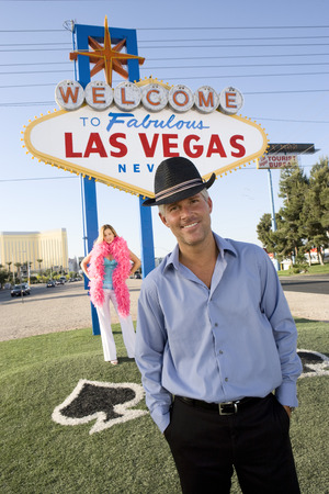 Portrait of mid-adult man in front of Welcome to Las Vegas sign, mid-adult woman behind. Stock Photo - 5476291