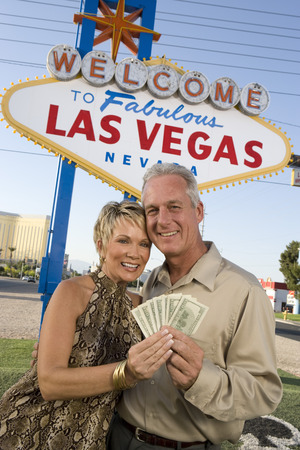 lucky man: Middle-aged couple in front of Welcome to Las Vegas sign, portrait