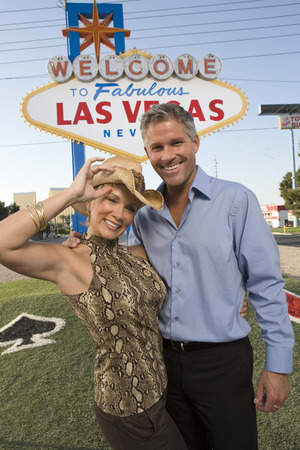 Middle-aged woman and mid-adult man in front of Welcome to Las Vegas sign, portrait