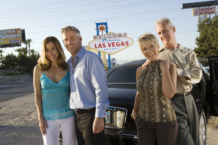 Two women and two men posing in front of Welcome to Las Vegas sign, group portrait Stock Photo - 5476302