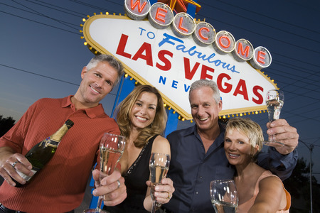 western script: Two women and two men posing in front of Welcome to Las Vegas sign, group portrait.