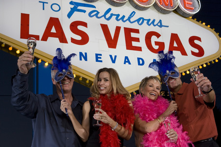 Two women and two men posing in front of Welcome to Las Vegas sign, group portrait Stock Photo - 5476318