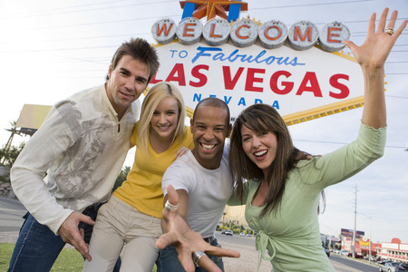 Two women and two men in front of Welcome to Las Vegas sign, group portrait Stock Photo - 5476332