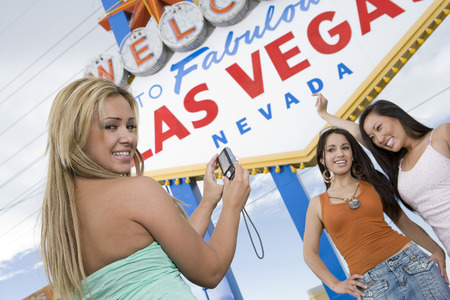 welcome sign: Three women taking picture in front of Las Vegas welcome sign, Nevada, USA