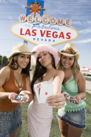 welcome sign: Women holding cards and gambling chips in front of Las Vegas welcome sign, Nevada, USA LANG_EVOIMAGES