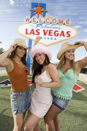 welcome sign: Women posing in front of Las Vegas welcome sign, Nevada, USA