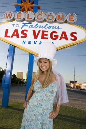 welcome sign: Femme posant devant des Las Vegas Bienvenue signe, au Nevada, �.-u. LANG_EVOIMAGES