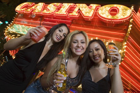 Portrait of three young women toasting in front of illuminated casino, Las Vegas, Nevada, USA Stock Photo - 5476402